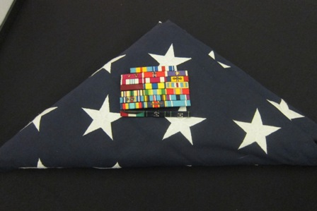 Folded U.S.  flag and medals of a fallen U.S. Navy Seal Team member